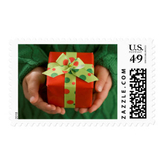 Child's hands holding a present postage stamp