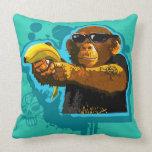 Chimpancé que sostiene un plátano cojines