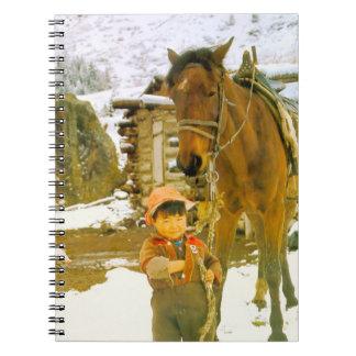 China en invierno - niño pequeño con un caballo libros de apuntes