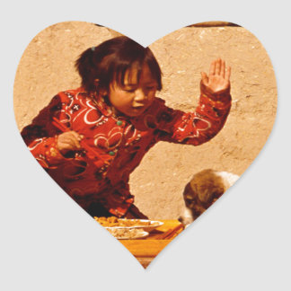 Chinese children playing with a dog heart sticker