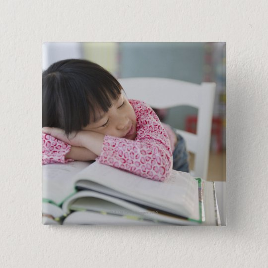 Chinese girl napping on textbooks button