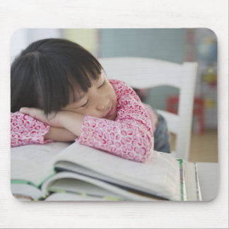 Chinese girl napping on textbooks mouse pad