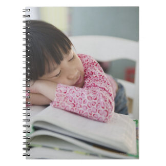 Chinese girl napping on textbooks note book