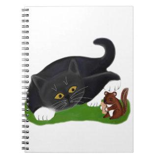 Chipmunk Holds a Peanut as Tuxedo Kitten Pats its Notebook