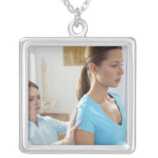 Chiropractic examination of the thoracic spine. silver plated necklace
