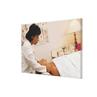 Chiropractor de sexo femenino que da masajes a un impresión en tela