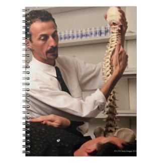 Chiropractor y paciente libros de apuntes con espiral