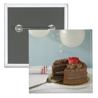 Chocolate cake with missing slice on table, button