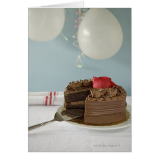 Chocolate cake with missing slice on table, card