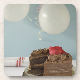 Chocolate cake with missing slice on table, beverage coaster