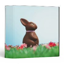 Chocolate Easter bunny amongst flowers in grass, Binder
