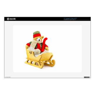 Christmas bear in wooden sleigh on white laptop skin