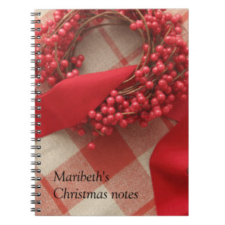 Christmas berries and wreath on plaid notebook