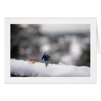 Christmas Card: Tiny People Sledging in the Snow Greeting Card