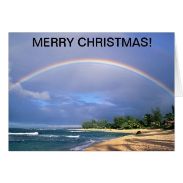 Christmas card with a perfect rainbow over a beach