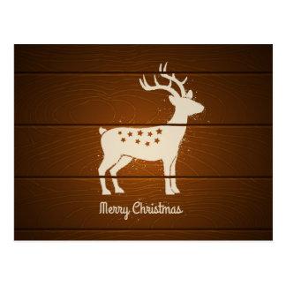 Christmas deer on wooden background postcard