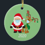"""Christmas Face Mask Santa and Reindeer 2020 Ceramic Ornament<br><div class=""""desc"""">This design was created though digital art. It may be personalized in the area provided or customizing by changing the photo or added your own words. Contact me at colorflowcreations@gmail.com if you with to have this design on another product. Purchase my original abstract acrylic painting for sale at www.etsy.com/shop/colorflowart. See...</div>"""