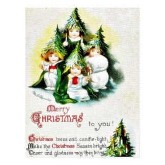 Christmas greeting with kids wearing christmas tre postcard