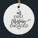 """Christmas Tree Our First Christmas Engaged Ceramic Ornament<br><div class=""""desc"""">This christmas tree """"our first christmas engaged"""" holiday ornament is the perfect romantic christmas tree decoration. The design features a diamond ring,  and the words """"our first christmas engaged"""" with the year all arranged to look like a christmas tree.</div>"""