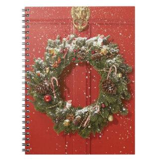 Christmas wreath hanging on a door note book