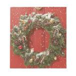 Christmas wreath hanging on a door notepad