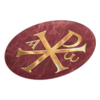 Christogram de oro en fondo de mármol rojo platos