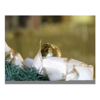 Chuchería de oro del navidad con la cinta blanca postal