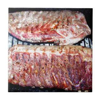 Chuletas de cerdo del cerdo en la parrilla azulejo
