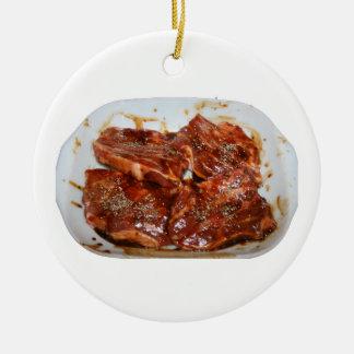 Chuletas de cerdo en la fotografía blanca del adorno navideño redondo de cerámica