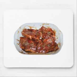 Chuletas de cerdo en la fotografía blanca del plat mousepads