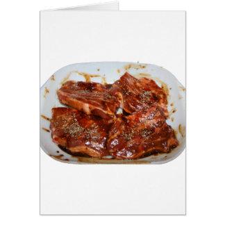 Chuletas de cerdo en la fotografía blanca del tarjeta pequeña