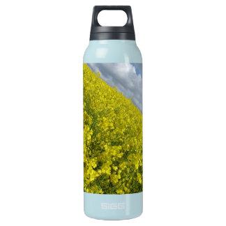 Cielo azul y nublado del agaisnt amarillo de la botella isotérmica de agua