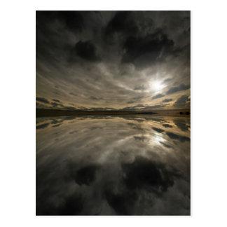 Cielo tempestuoso reflejado en agua tarjetas postales