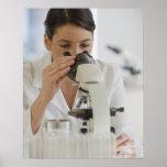 Científico que usa el microscopio en farmacéutico posters