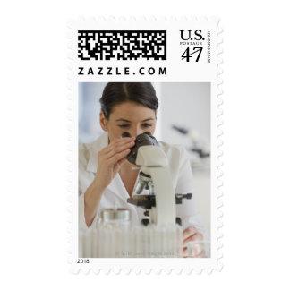 Científico que usa el microscopio en farmacéutico sello