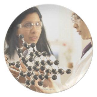 Científicos que examinan el modelo molecular plato de cena