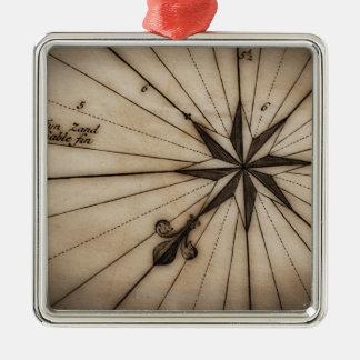 Cierre para arriba del rosa de viento en mapa adorno navideño cuadrado de metal