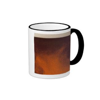 Ciérrese encima de imagen de la cerveza ambrina co tazas de café