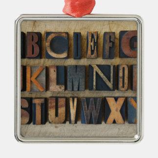 Ciérrese para arriba de alfabeto en la prensa de adorno navideño cuadrado de metal