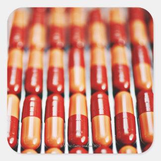 Ciérrese para arriba de filas de las cápsulas de pegatina cuadrada