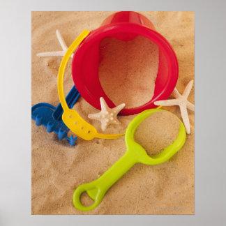 Ciérrese para arriba de juguetes en la arena posters