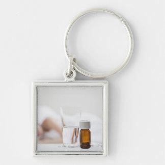 Ciérrese para arriba de la botella de píldora con  llavero cuadrado plateado