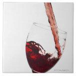 Ciérrese para arriba del vino rojo que es vertido  azulejo cuadrado grande