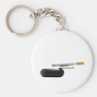 Cigarrillo en el cenicero sobre blanco llavero