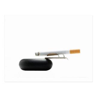 Cigarrillo en el cenicero sobre blanco postal