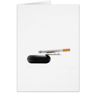 Cigarrillo en el cenicero sobre blanco tarjeta de felicitación