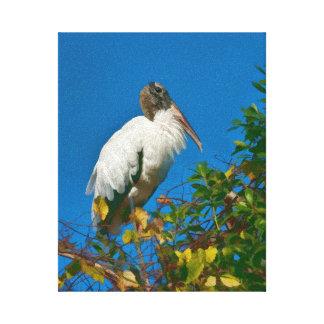 Cigüeña de madera en un árbol impresion de lienzo