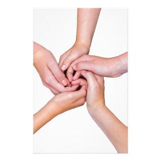 Cinco brazos adolescentes con las manos enredadas papelería
