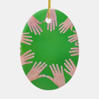 Cinco manos de los niños que se unen a en círculo adorno navideño ovalado de cerámica