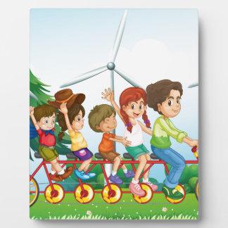 Cinco niños que montan en la bici cerca de los placa de madera